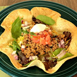 Quick Turkey Taco Salad Recipe - Cook ground turkey with prepared taco seasoning and bell pepper to put atop piles of salad greens and tortilla chips to make a quick and easy taco salad.