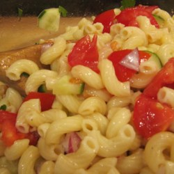 Mom's Macaroni Salad Recipe - Juicy tomato and crunchy cucumber are tossed with onion and macaroni, then dressed with a tangy blend of vinegar, sugar, mustard, olive oil, garlic powder, salt and pepper. Let the salad chill before serving.