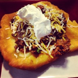 Oklahoma Indian Tacos Recipe - Easy-to-make fry bread needs just two ingredients, self-rising flour and buttermilk. Top the golden brown fried breads with a spicy ground beef and bean mixture, then garnish with your favorite taco trimmings.
