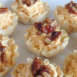 Pumpkin Cheese Tarts with Pecans and Cinnamon Sea Salt Recipe - These savory tarts with cream cheese, Cheddar, and pumpkin are topped with a pinch of cinnamon sea salt and buttery toasted pecans for an elegant holiday appetizer.