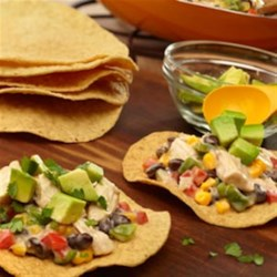 Creamy Chicken Tostadas Recipe - These tasty tostadas feature a combination of cooked chicken, onion, peppers, corn, black beans and creamy poblano and queso soup. Topped with fresh cilantro and a delicious avocado mixture, you won't be able to resist the incredible flavor!