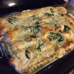 Chicken and Spinach Alfredo Lasagna Recipe - Savory shredded chicken layered with fresh spinach, creamy Alfredo sauce, melted mozzarella, ricotta, Parmesan cheese and lasagna noodles.