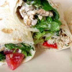 Warm Chicken Ranch Wraps Recipe - These sandwiches-on-the-go are a full meal deal: grilled or fried chicken, tomatoes, lettuce and rice pilaf in a creamy ranch dressing snugly wrapped in a warm tortilla.