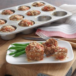 Weeknight Mini Meatloaves Recipe - This is an individual meatloaf recipe with Hunt's(R) Tomatoes and Kraft(R) Parmesan added to the meat and baked in muffin cups.