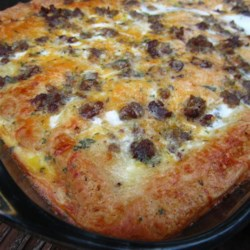 Christmas Breakfast Pizza Recipe - Sausage, eggs, crescent rolls, and cheese snuggle down in a casserole, chill overnight, and bake in the morning in this recipe for Christmas breakfast pizza.