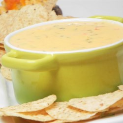 Queso (Cheese) Dip Recipe - Poblano, Anaheim, and jalapeno peppers combine with melted cheese to make this tasty queso dip appetizer with a kick! It's perfect for watching football.
