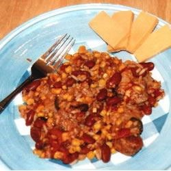 Mexican Pork Chops Recipe - Tender pork chops are cooked up Mexican-style with tomatoes, corn, beans, and rice.