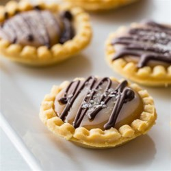 Mini Salted Caramel Chocolate Pies Recipe - Mini tart shells filled with layers of caramel and ganache are drizzled with more dark chocolate and topped with sea salt crystals for an elegant dessert.