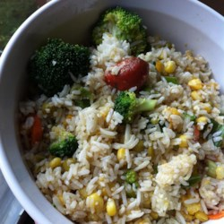 Cold Rice Salad Recipe - White rice tossed with broccoli, tomatoes, peas, corn, hard-cooked eggs, and chicken, dressed with a simple vinaigrette. Serve chilled with fruit and rolls.