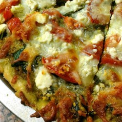Fresh Pesto Pizza Recipe - Use a pre-baked whole wheat pizza crust, some prepared pesto sauce, and toppings of fresh spinach, tomato, and 2 kinds of cheese to make a vegetarian pizza that's on the table in just a few minutes.