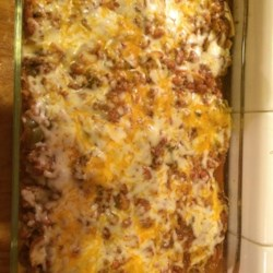 Cheesy Chilada Casserole Recipe - This easy Mexican-style casserole recipe has layers of seasoned ground beef with beans in a tomato sauce, cheese, and tortillas for a tasty dinner option.