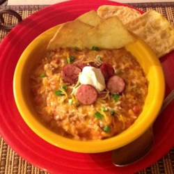 Creamy Spanish Rice Soup Recipe - Spanish rice combined with tomato soup, cream cheese, sausage, and peppers make a hearty soup that will please everyone in the family.