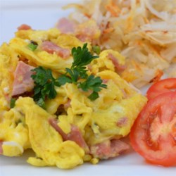 Sharon's Egg and Ham Scramble Recipe - Ham and eggs get dressed up with jalapeno pepper, Cheddar cheese, and apple-smoked ham in this hearty breakfast scramble.