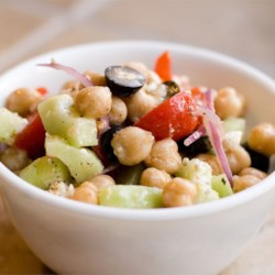 Greek Garbanzo Bean Salad Recipe - Just what a Greek salad should be, chock full of hearty ingredients like tomatoes, cucumbers, olives, feta cheese, and of course beans, and done up with a zesty dressing.