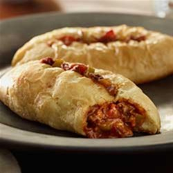 Mini Chili Calzones Recipe - Wrapped in crescent dough, these easy mini calzones are filled with chili, bell pepper, bacon, and Cheddar cheese.
