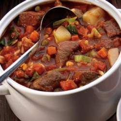 Home Style Beef Stew Recipe - Comfort food at its best! While you slave away at work, dinner is simmering away at home in your slow cooker.  Hearty beef with veggies, potatoes, our Red Gold(R) Fresh Squeezed Tomato Juice and Red Gold(R) Diced Tomatoes with Garlic and Olive Oil – guaranteed to warm your chilled bones!
