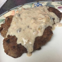 Quick Country-Fried Steak Recipe - Country-fried steak has the old-country taste right in your own home. Serve with mashed potatoes and peas for a hearty meal.