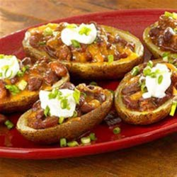 Super Loaded Chili Potato Skins Recipe - Potato skins are baked until crisp, then filled with chili and cheese and topped with sour cream and chopped green onions.