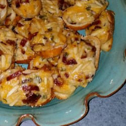 Almond Cheddar Appetizers Recipe - Bacon, Cheddar cheese, almonds, and green onions are mixed in mayonnaise to be spread on bread and baked for finger-food appetizers.