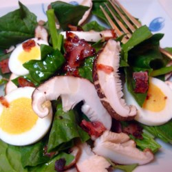 Spinach and Mushroom Salad Recipe - Spinach, crumbled bacon, and mushrooms are topped with a warm tangy dressing in this delicious salad.
