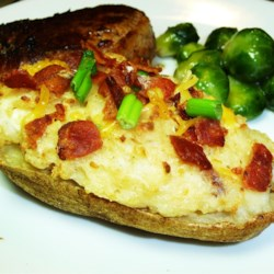 Cheesy Twice-Baked Potatoes Recipe - These twice-baked potatoes are given a creamy and cheesy texture through the addition of sour cream and Monterey Jack cheese.