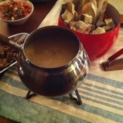 The Best Swiss Cheese and Beer Fondue Recipe - Traditionally made with wine, this version of a Swiss fondue features beer for a more robust flavor that will keep everyone dipping anything they can find.