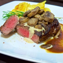 Filet Mignons With Pepper Cream Sauce Recipe - Delectable filet mignons get a coating of crushed peppercorns, then are cooked to perfect doneness and served with a velvety cream sauce to take the peppery bite down a notch.