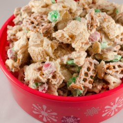 Reindeer Munch Recipe - Kids young and old will love this reindeer munch, made with rice cereal squares, pretzel sticks, peanuts, and candy-coated milk chocolate pieces, then drizzled with a white chocolate topping.
