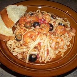 Linguine Pescadoro Recipe - A lively simmer of garlic, thyme, tomatoes, olives, clam juice and red pepper flakes makes a flavorful base for fresh shrimp, scallops and baby clams, perfect with hot linguini. Hint: discard any clams that do not open after they simmer.