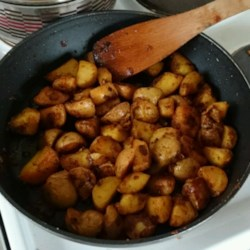 Indian Curry Potato Fries Recipe - Potato cubes are fried in Indian-inspired spices for a perfect accompaniment to a curry dish. Serve alongside tamarind chutney for dipping.