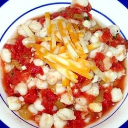 Mexi Hominy Recipe - Hominy combines with diced tomatoes, green chiles, cumin, garlic, and cilantro in this tasty dish. Top it with Monterey Jack cheese, if you like.