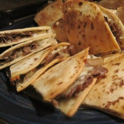 Philly Cheesesteak Quesadillas Recipe - Philly cheesesteak meets quesadillas when steak, bell peppers, onions, and Cheddar cheese are baked between tortillas.
