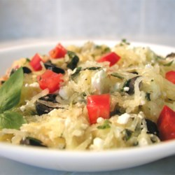Spaghetti Squash I Recipe - Strands of baked spaghetti squash tossed with feta cheese, onions, tomatoes, olives, and basil for a Greek-inspired dish that tastes like pasta without all the calories.