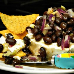 Easy Layered Black Bean Dip Recipe - Black beans, cream cheese, lime juice, and a blend of spices make this recipe for layered black bean dip a guaranteed crowd-pleaser!