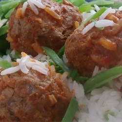 Slow Cooker Porcupine Meatballs With Peppers Recipe - Meatballs studded with rice cook for hours in a slow cooker with tomato sauce and peppers.