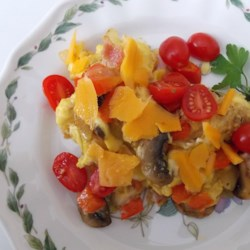 Extreme Veggie Scrambled Eggs Recipe - Scrambled eggs with Cheddar cheese get an extra boost of color when bell peppers, black beans, and tomatoes are added to the mix.