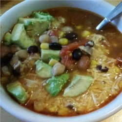 Spicy Tortilla Bean Soup Recipe - Spicy tortilla soup with plenty of beans and spices is a warm meal to serve on cold winter evenings. Add lime juice, Cheddar cheese, and avocado!