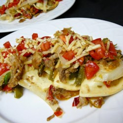 Smothered Pierogies Recipe - Sausage, onions, peppers and mushrooms turn frozen pierogies into a delicious treat. Try experimenting with different sausages, vegetables and cheeses.