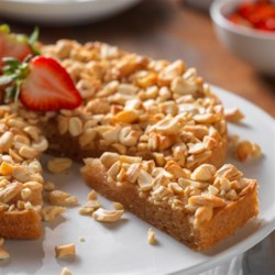 Lemony Cashew Cake with Fresh Strawberries Recipe - This single-layer lemon cake is baked with a topping of chopped cashews. Serve with sliced strawberries for a festive touch!