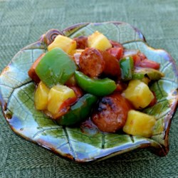 Sweet and Sour Sausage Recipe - Smoked sausage simmers in a sweet and tangy sauce, made with apricot preserves, pineapple chunks, and stewed tomatoes, in this easy dish.
