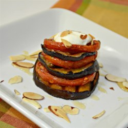 Roasted Eggplant and Tomato Towers Recipe - Roasted eggplant and tomatoes are layered on a plate topped with yogurt, honey, and almonds for a colorful and fancy appetizer or main dish salad.