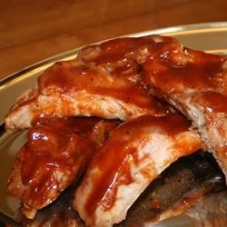 Oven Baked BBQ Ribs Recipe - These tender and flavorful ribs are baked and basted for 3 hours in a delicious tangy sauce.