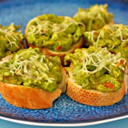 Cheesy Avocado Bites Recipe - Baguette slices are topped with avocado, tomatoes, and cheese and baked into tasty little appetizer bites.