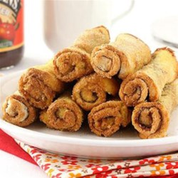 French Toast Roll-Ups from Musselman's(R) Apple Butter Recipe - These breakfast roll-ups with apple butter and cinnamon are baked until golden brown then served with a creamy dipping sauce.