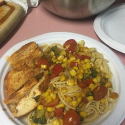 Rainforest Chicken and Pasta Recipe - Seasoned chicken breasts are grilled, sliced, and served over fettuccine pasta with a cooked corn and tomato salsa. There's a bit of Cajun heat in this recipe.