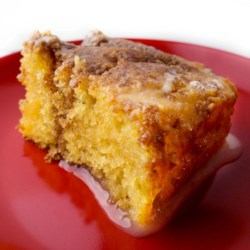 Cinnamon Honeybun Cake  Recipe - This easy cinnamon-flavored cake, made with a box of yellow cake mix and a few simple additions, has a syrupy icing poured over it before serving.