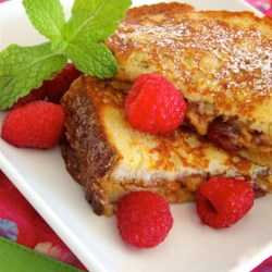 PBJ French Toast Recipe - A peanut butter and jelly sandwich is dipped in a raspberry liqueur-infused batter and pan-fried into a peanut butter and jelly French toast treat.