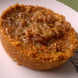 Graham Crust Butter Tarts Recipe - Graham cracker crust creates a new-style butter tart with traditional filling and optional raisins and nuts.