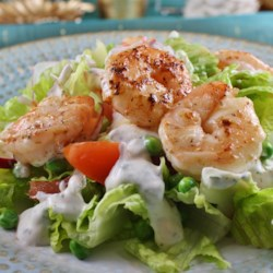 Warm Shrimp Salad Recipe - The gently sauteed shrimp are combined with butter lettuce, tomatoes, avocado, cucumbers, and shredded carrots, and then topped with your favorite dressing.