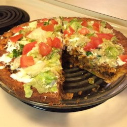 Quick Crescent Taco Pie Recipe - Triangles of crescent roll dough are pressed into a 10-inch pie tin and layered with all the taco fixings. First come the corn chips, followed by the ground meat, sour cream and cheese. Then another layer of corn chips finishes the pie. It 's baked until golden, cut into slices and served with shredded lettuce and slices of avocado.